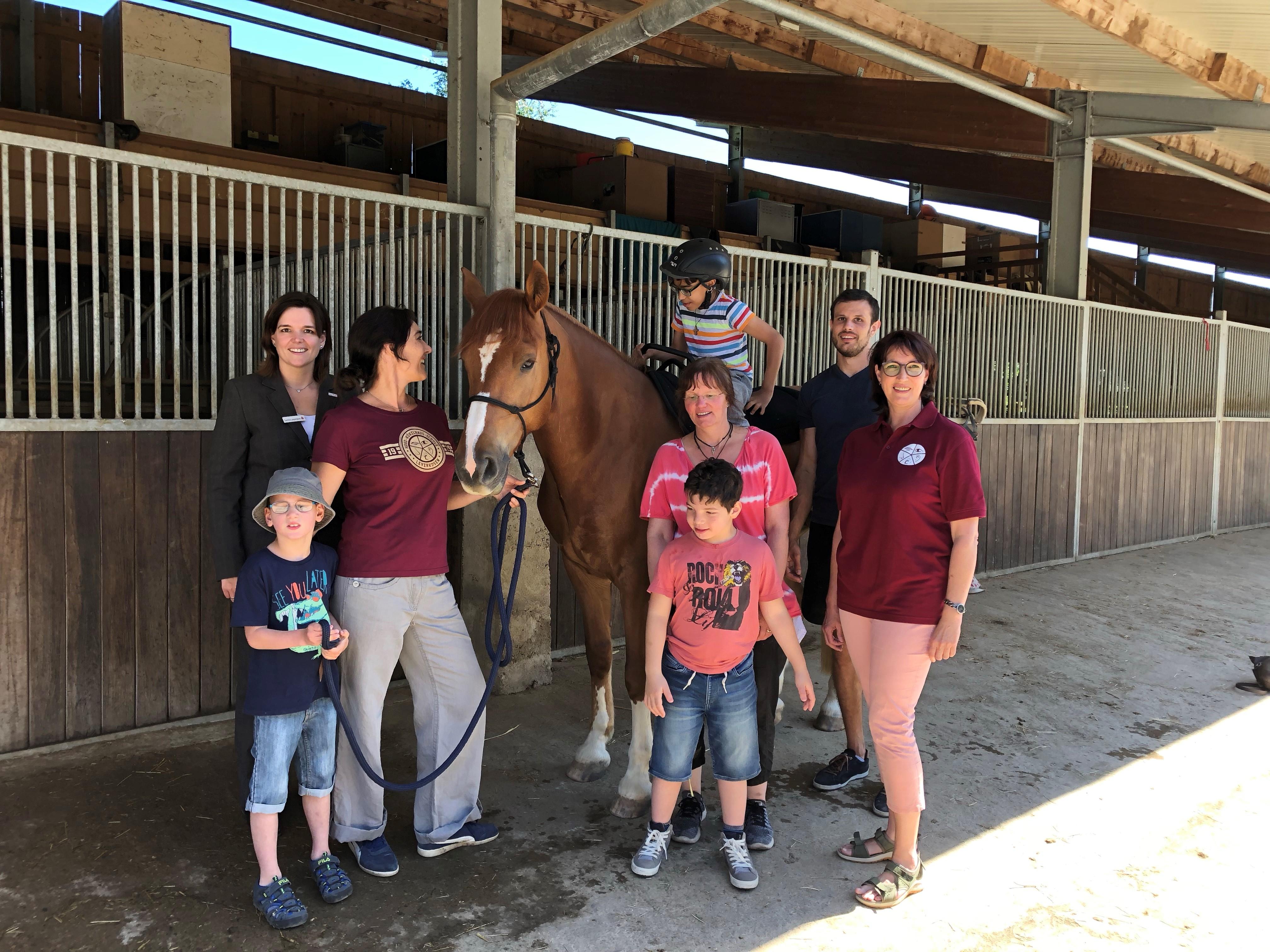 Kinder und Erwachsenen im Stall neben einem Pferd