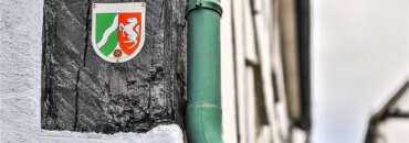 Das NRW Wappen neben einer Regenrinne